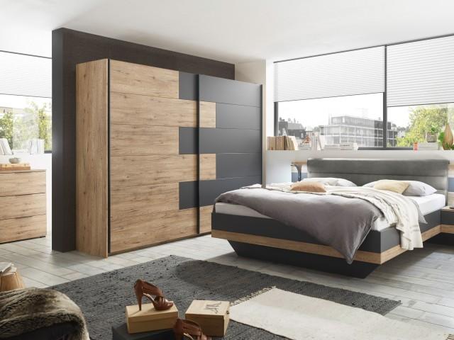 <p>Schlafzimmer in Dekorfolie Bartex Eiche/Absetzungen graphit, bestehend aus Kleiderschrank 2-trg., BHT 270x210x60cm und Bettanlage, Liegefl&auml;che 180x200cm, inklusive 2 Nachtkommoden und gepolstertem Kopfteil.</p>